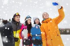 Amis heureux avec les surfs des neiges et le smartphone Photo libre de droits