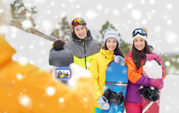Amis heureux avec les surfs des neiges et le smartphone Photographie stock libre de droits