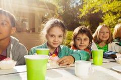 Amis heureux avec les tasses et les petits gâteaux colorés Photo stock