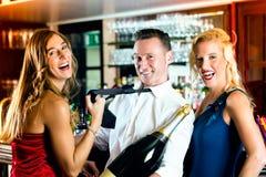 Amis heureux avec un champagne de bouteille au bar Image libre de droits