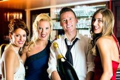 Amis heureux avec un champagne de bouteille au bar Photos stock