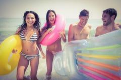 Amis heureux ayant l'amusement à la plage Photos stock