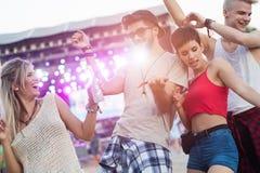 Amis heureux ayant l'amusement au festival de musique Images stock
