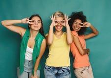 Amis heureux ayant l'amusement au fond bleu Photo stock