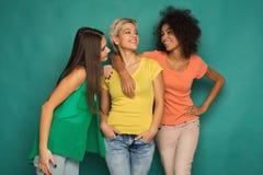 Amis heureux ayant l'amusement au fond bleu Photographie stock libre de droits