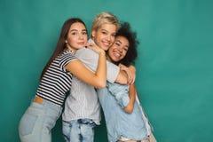 Amis heureux ayant l'amusement au fond bleu Photos stock