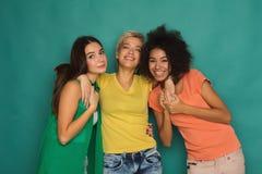 Amis heureux ayant l'amusement au fond bleu Image libre de droits