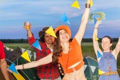 Amis heureux ayant l'amusement au terrain de camping dans la soirée Images stock