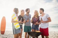 Amis heureux ayant l'amusement autour du barbecue Images stock