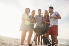 Amis heureux ayant l'amusement autour du barbecue Photo libre de droits