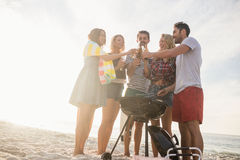 Amis heureux ayant l'amusement autour du barbecue Photographie stock