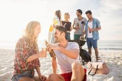 Amis heureux ayant l'amusement autour du barbecue Image stock