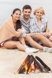 Amis heureux ayant l'amusement autour du feu Photos libres de droits