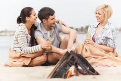 Amis heureux ayant l'amusement autour du feu Image stock