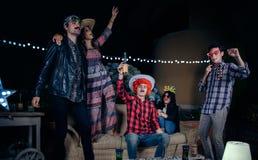 Amis heureux ayant l'amusement avec des costumes dans une partie Photographie stock libre de droits