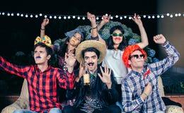 Amis heureux ayant l'amusement avec des costumes dans une partie Photos libres de droits