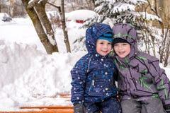Amis heureux ayant l'amusement avec la neige Photographie stock libre de droits