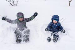 Amis heureux ayant l'amusement avec la neige Image libre de droits