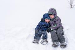 Amis heureux ayant l'amusement avec la neige Images libres de droits