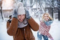 Amis heureux ayant l'amusement avec la neige dans le parc Photo stock