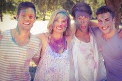 Amis heureux ayant l'amusement avec la peinture de poudre Photo stock