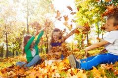 Amis heureux ayant l'amusement avec les feuilles jetées Images stock