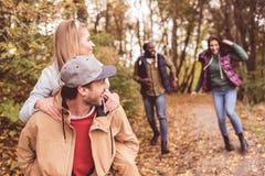 Amis heureux ayant l'amusement dans la forêt Images stock