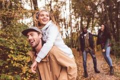 Amis heureux ayant l'amusement dans la forêt Photographie stock