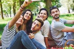 Amis heureux ayant l'amusement dehors en nature Photographie stock libre de droits