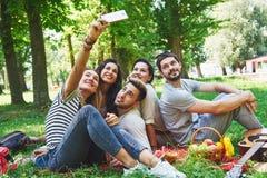 Amis heureux ayant l'amusement dehors en nature Image libre de droits