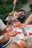 Amis heureux ayant l'amusement dehors, mains grillant le verre de vin rosé Image stock