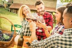 Amis heureux ayant l'amusement et buvant du vin - concept d'amitié Images stock