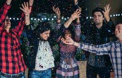 Amis heureux ayant l'amusement parmi les confettis de partie Images libres de droits
