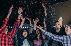 Amis heureux ayant l'amusement parmi les confettis de partie Photographie stock libre de droits