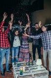 Amis heureux ayant l'amusement parmi les confettis de partie Photo stock