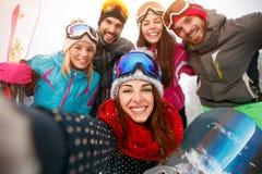 Amis heureux ayant l'amusement sur la neige Snowbarders et groupe t de skieurs Photos libres de droits