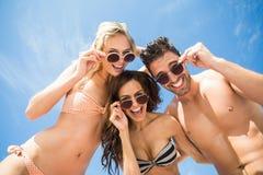 Amis heureux ayant l'amusement sur la plage Photographie stock libre de droits