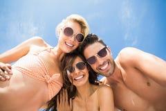 Amis heureux ayant l'amusement sur la plage Image stock