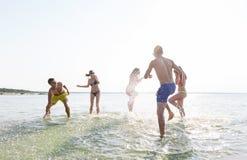 Amis heureux ayant l'amusement sur la plage d'été Photo libre de droits