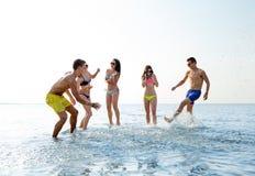 Amis heureux ayant l'amusement sur la plage d'été Image libre de droits