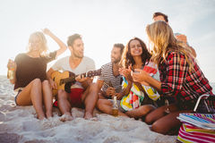 Amis heureux ayant l'amusement tout en se reposant sur le sable Image stock