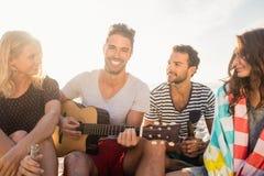 Amis heureux ayant l'amusement tout en se reposant sur le sable Photo stock
