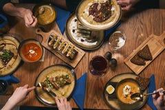 Amis heureux ayant la nourriture et les boissons gentilles Photographie stock