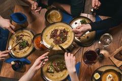 Amis heureux ayant la nourriture et les boissons gentilles Image libre de droits