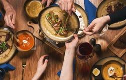 Amis heureux ayant la nourriture et les boissons gentilles Photographie stock libre de droits
