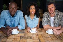 Amis heureux ayant le café à la table en bois en café Photographie stock libre de droits