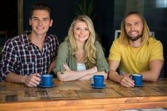Amis heureux ayant le café à la table en bois en café Images stock