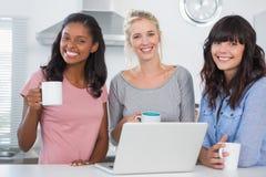 Amis heureux ayant le café ainsi que l'ordinateur portable Image libre de droits
