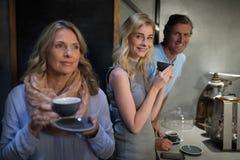 Amis heureux ayant le café au compteur de café Image stock