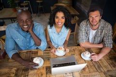 Amis heureux ayant le café avec l'ordinateur portable sur la table en bois en café Photographie stock libre de droits